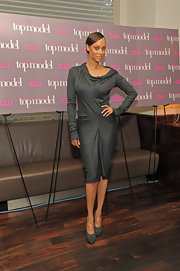 Tyra showed off her figure in a form fitting cocktail dress and matching grey suede pumps.