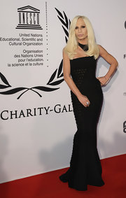 Donatella looks wicked stylish in this floor length Versace gown.  Her bright blond locks stand out against her black gown with a curve flattering silhouette.