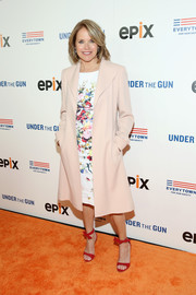 Katie Couric arrived for the New York premiere of 'Under the Gun' wearing a nude duster coat over a floral dress.