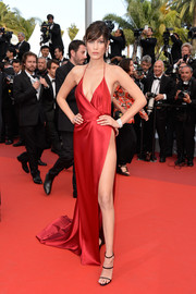 Bella Hadid looked quite the bombshell in a red Alexandre Vauthier Couture halter gown with a plunging neckline and a waist-high slit during the Cannes premiere of 'The Unknown Girl.'