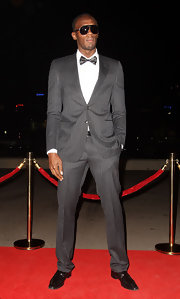 Usain looks uber dapper in a charcoal gray pinstriped suit and bowtie.