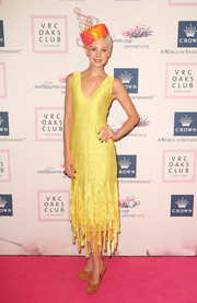 Kate Peck piled on the brights for the VRC Oaks Club luncheon, teaming a yellow dress with an orange headpiece and mustard platform pumps.