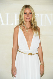 Gwyneth Paltrow styled her white Grecian gown with a gold chain belt when she attended the Valentino Couture Fall 2019 show.