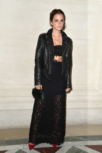 Emma Watson toughened up her lace crop-top and skirt combo with a black Valentino leather jacket when she attended the label's fashion show.