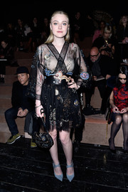 Dakota Fanning looked exotic in a sheer, kimono-style Valentino mini dress with cosmic-inspired embellishments during the brand's fashion show.
