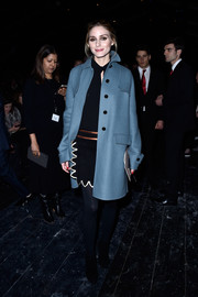 Olivia Palermo headed to the Valentino fashion show wearing a stylish blue coat over a little black dress.