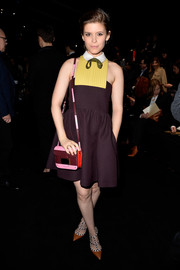 Kate Mara went for youthful charm at the Valentino fashion show in a plum mini dress with a yellow bib and a white collar.