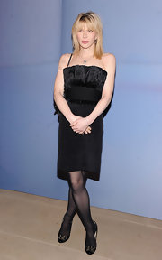 Courtney Love opted for a demure black dress paired with embellished pumps.