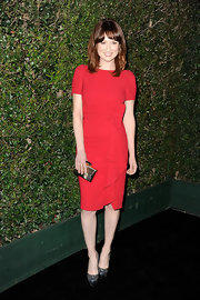 Ellie Kemper accessorized her red dress at the Valentino store opening with this gold box clutch.