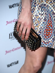 A studded clutch added some edge to Katie Aselton's girlie paisley dress at the 2013 Vanities Calendar celebration.