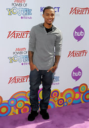 The young rapper wears a casual v-neck hooded sweater with for this laid back look.