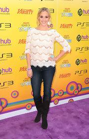 Andrea Bowen looked chic on the red carpet in a lacy top paired with dark jeans and black suede knee-high boots.