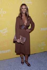 Sticking to an all-brown look, Iman accessorized with a Michael Kors Miranda clutch.
