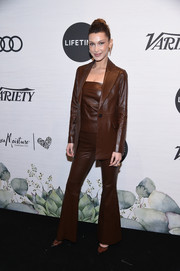 Bella Hadid complemented her suit with brown PVC pumps by Gianvito Rossi.