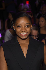 Simone Biles attended the Vera Wang fashion show wearing her hair in a braided side bun.