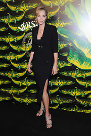 Uma Thurman added a touch of dazzle to her all-black ensemble with metallic embellished strappy sandals.