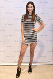 Victoria Justice made clashing patterns work with this fishnet stockings and striped dress combo.