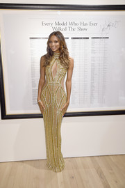 Jasmine Tookes flaunted her fabulous physique in a glittery gold cutout gown during the Victoria's Secret Bright Night Fantasy Bra reveal.