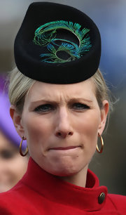 Zara Phillips stayed true to the English tradition of decorative hats with this tear drop shaped hat with a curled peacock feather.