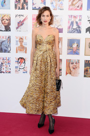 Alexa Chung looked ultra chic in a richly textured strapless gold dress by Prada at the Vogue 100 Festival Gala.