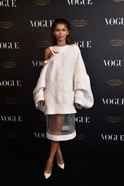 Zendaya Coleman attended the Vogue 95th anniversary party wearing a white Katherine Mavridis SS16 dress with billowing long sleeves and matching white Jimmy Choo pumps.