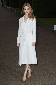 Lily James injected a bit of shimmer via a pair of strappy gold platform sandals, also by Ralph Lauren.
