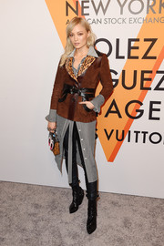 Pom Klementieff layered like a pro in this brown suede jacket, striped shirtdress, and skinny pants combo for the 'Volez, Voguez, Voyagez' exhibition opening.
