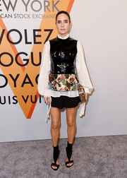 Jennifer Connelly layered a black patent and floral-print peplum top over a white blouse, both by Louis Vuitton, for an edgy-chic look during the 'Volez, Voguez, Voyagez' exhibition opening.