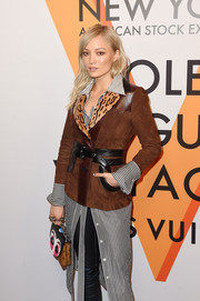 Pom Klementieff attended the 'Volez, Voguez, Voyagez' exhibition opening carrying a Louis Vuitton Pochette Kabuki purse.