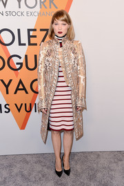 Lea Seydoux donned a gold Louis Vuitton jacquard coat for a chicer finish to her striped turtleneck dress at the 'Volez, Voguez, Voyagez' exhibition opening.