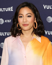 Constance Wu added more color to her outfit with a pair of orange Alison Lou hoops.