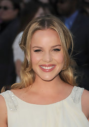 Abbie Cornish's half up, half down 'do can be recreated by first setting hair in hot rollers. Next, create a center part, leave out some face-framing strands and pull back all the hair, from the top of the head to above the ears. Instead of securing with a hair elastic, section out two-inch pieces from the sides and pin in back of the ears. Let the remaining hair fall in curls over the pins.