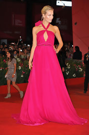 A bright fuchsia gown with a halter neckline and a front cutout on the bust was a bright and feminine choice for Natasha Poly.