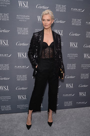 Underneath her jacket, Karlie Kloss looked alluring in a black lace corset top.