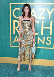 Gemma Chan finished off her dazzling ensemble with a boxy blue satin purse.