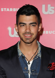 Joe Jonas accented his tailored blazer with a silver box chain necklace with claw amulat.