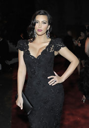 Kim Kardashian matched her dramatic Old Hollywood vibe with a lacy gown and black satin clutch.