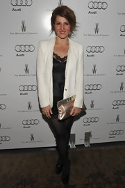 Nia Vardalos gave her monochromatic party attire a shiny finish with a rose gold metallic clutch.