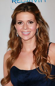 Carly Steel opted for a half up hairstyle full of loose curls. She highlighted her look with dangling diamond earrings.