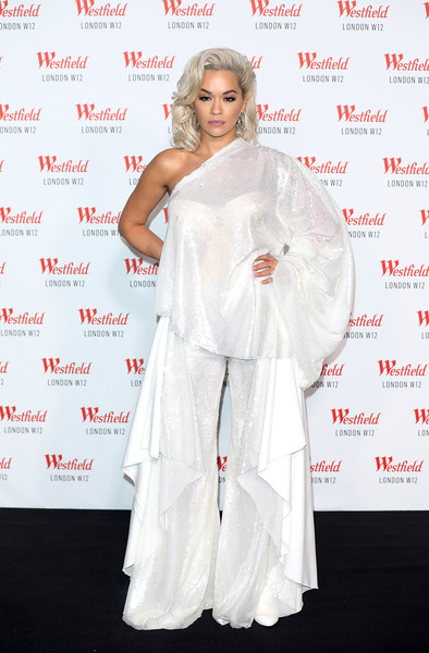 Rita Ora attended Westfield London's 10th anniversary celebration wearing a loose white one-shoulder blouse by Paula Knorr.