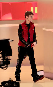 Justin wears a red and black leather jacket in the stylings of a denim jacket for his showing in Germany.