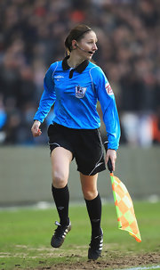 Referee Sian Massey keeps pace with a black pair of Adidas cleats.