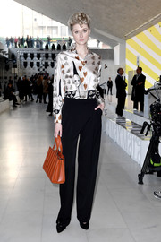 Elizabeth Debicki paired a printed silk blouse with black trousers for the Max Mara show.