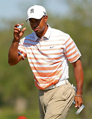 Not only did Tiger show his love of his sponsor, but he showed his love of color with this white and orange striped polo.