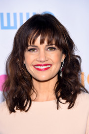 Carla Gugino styled her hair in a tousled wavy look with sweeping bangs.
