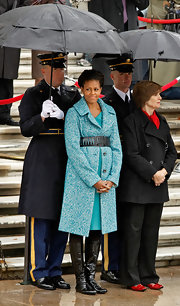 Michelle Obama fastened her coat with an oversized black cutout belt during a commemoration of Veterans Day.