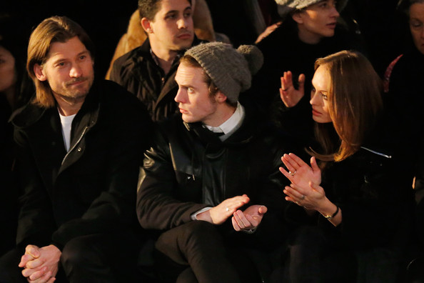 Sam Claffin kept warm in the NYC winter while watching a runway show at Fashion Week with a knit beanie with pom on top.