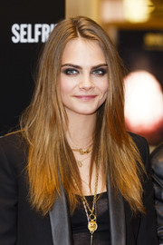 Cara Delevingne wore her long hair down in an edgy, straight style during the YSL Loves Your Lips party.