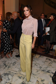 Victoria Beckham attended the YouTube cocktail party during Paris Fashion Week wearing a sheer dusty-pink turtleneck blouse from her label.
