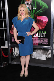 Megan Hilty finished off her eye catching blue cowl neck dress with a versatile black envelope clutch.